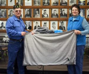 Mike and Shirley Johnson hold up an electric shoulder throw at The American Legion Wells-Hussey Post No. 42 in Damariscotta. The post donated several of the heated throws to the Togus Springs Hospice Unit in Augusta. (Jessica Picard photo)