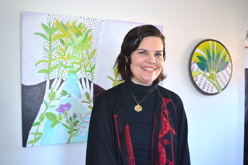 "Emily Sabino stands before two of the paintings in her ""Healing Hands"" show. At left is ""Self-Portrait."" (Christine LaPado-Breglia photo)"