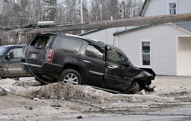 A utility pole rests atop a GMC Yukon Denali SUV after a two-vehicle collision on Route 1 in Waldoboro on Tuesday, Feb. 12. Another SUV entering Route 1 did not yield the right of way, according to police. (Alexander Violo photo)