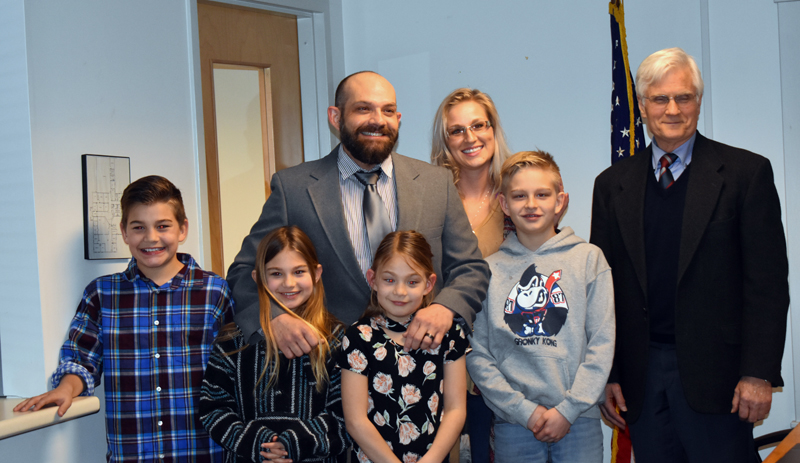 """Waldoboro Police Officer Dwight """"D.J."""" Jones stands with his family and Waldoboro Board of Selectmen Chair Robert Butler after taking his oath of office during a selectmen's meeting Tuesday, Feb. 26. (Alexander Violo photo)"""