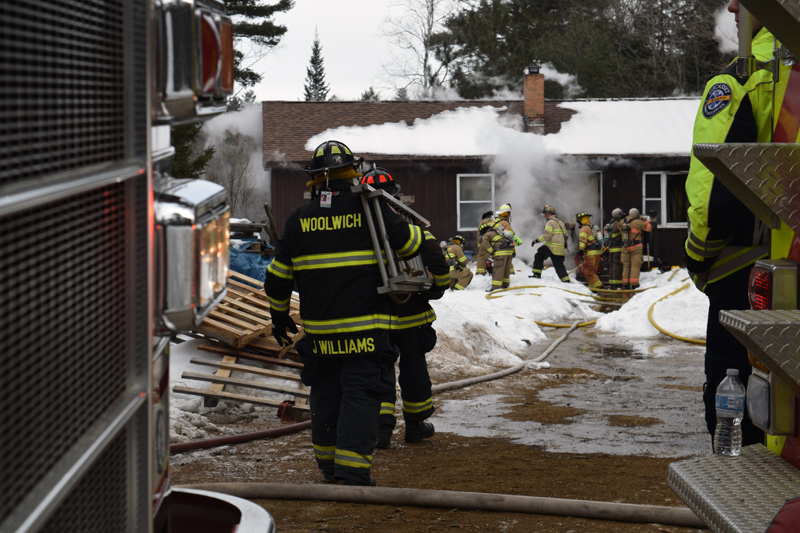 Woolwich firefighters carry a ladder toward a home on fire at 48 Greenleaf Road in Wesport Island on Wednesday, Feb. 27. (Jessica Clifford photo)