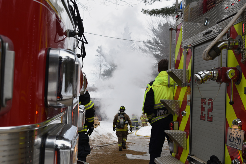 A firefigher walks toward a home on fire at 48 Greenleaf Road in Westport Island. (Jessica Clifford photo)