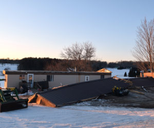 The metal roof of a mobile home at 45 Townhouse Road in Whitefield lies on the ground in front of the home Tuesday, Feb. 26 after blowing off during high winds the previous night. (Jessica Clifford photo)