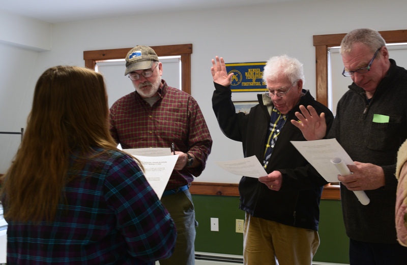 Alna Town Clerk Liz Brown administers the oath of office to (from left) Third Selectman Greg Shute, Second Selectman Doug Baston, and Road Commissioner Jeff Verney. (Jessica Clifford photo)