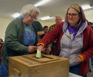 Melanie Gaczi (left) writes her vote on a slip of paper while Karen Silverman places her slip in the ballot box during a special town meeting at Pownalborough Hall in Dresden on Monday, March 11. Voters approved a change from electing to hiring town office staff, 41-14. (Jessica Clifford photo)