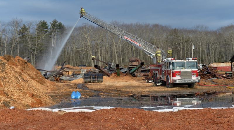 The Damariscotta ladder truck sprays water on hot spots at N.C. Hunt Lumber in Jefferson after daylight Saturday, March 30. (Paula Roberts photo)