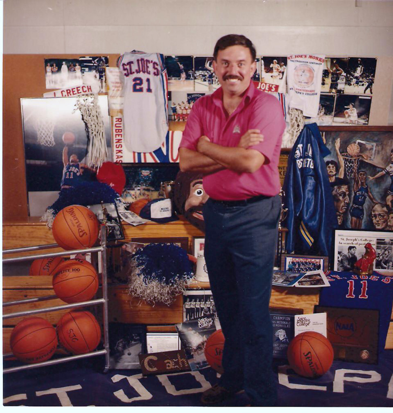 Rick Simonds poses for a photo in front of a collection of St. Joseph's College men's basketball memorabilia. The photo was the cover of the school's 1989-1990 media guide. (Photo courtesy St. Joseph's College Athletics)
