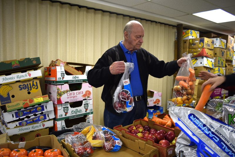 Earl Lemieux hands a bag of carrots and onions to a client at the St. Denis Food Pantry in Whitefield on Friday, March 1. Earl Lemieux and his late wife, Mary Lemieux, started the pantry more than 20 years ago. (Jessica Clifford photo)
