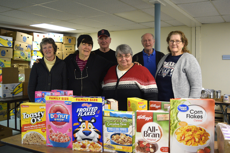 From left: St. Denis Food Pantry volunteers Janet Ober, Mabeline Small, Keith Sanborn, Lise Nickerson, Earl Lemieux, and Priscilla M. Sumabat pose for a photo in the pantry. Missing from the photo is Jeanne Shaw. (Jessica Clifford photo)