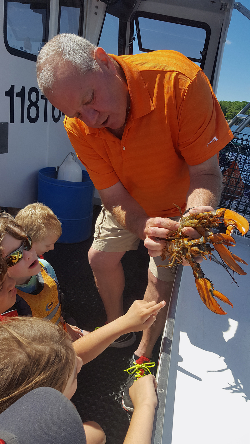 Lobsterman Tim Alley talks to Camp Mummichog campers about lobster anatomy on a camp field trip.