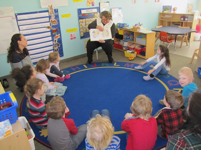 Patty Lane, of Bath Savings Institution, reads to children at Coastal Kids Preschool in Damariscotta.