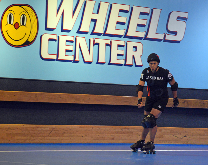 """Michael """"Hurry Kaine"""" Henderson skates for Casco Bay Roller Derby during a home game at Happy Wheels Skate Center in Portland on April 6. Henderson is the administrative assistant for the town of Dresden and a """"jammer"""" on the roller derby track. (Jessica Clifford photo)"""