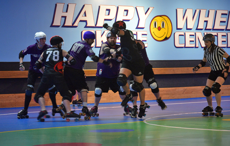 """Casco Bay Roller Derby's Michael Henderson jumps as he tries to establish """"lead jammer"""" position during a game against the Flour City Fear in Portland on April 6. (Jessica Clifford photo)"""