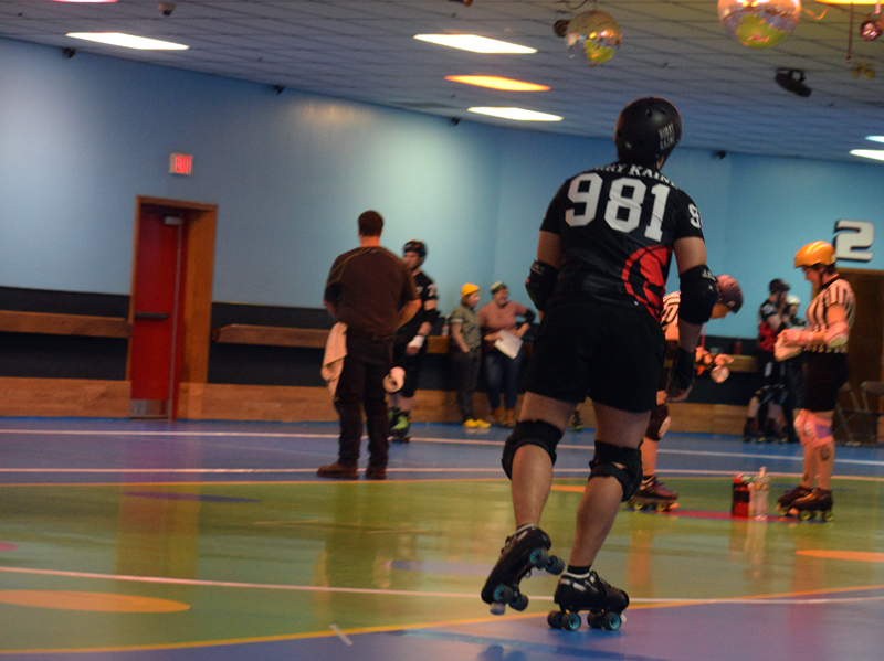 Michael Henderson skates onto the rink before a Casco Bay Roller Derby home game at Happy Wheels Skate Center in Portland on April 6. The back of his jersey bears his skate name, Hurry Kaine. (Jessica Clifford photo)