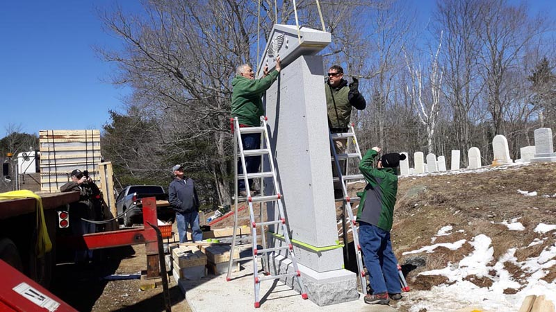 Eighty-two-year-old monument setter Francis Tash, of Barre, Vt., guides the top piece of a monument into place at West Bristol Cemetery in Walpole on Thursday, April 11. Thomas A. Stevens Cemetery Memorials, of Newcastle, and subcontractors worked throughout the day to set up South Bristol's new veterans memorial. (Candy Congdon photo)