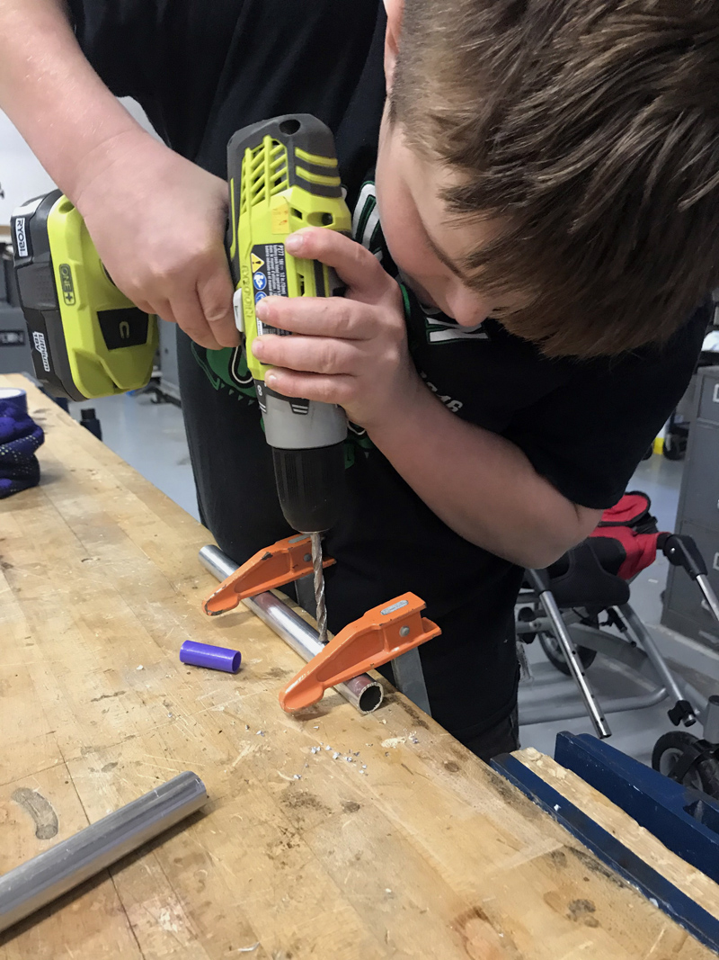 Camden Larrabee, 12, of Wiscasset, drills a hole in a metal tube, which he would go on to use as part of a pedal extension for another 12-year-old's wheelchair. (Photo courtesy Rachel Hamlin)