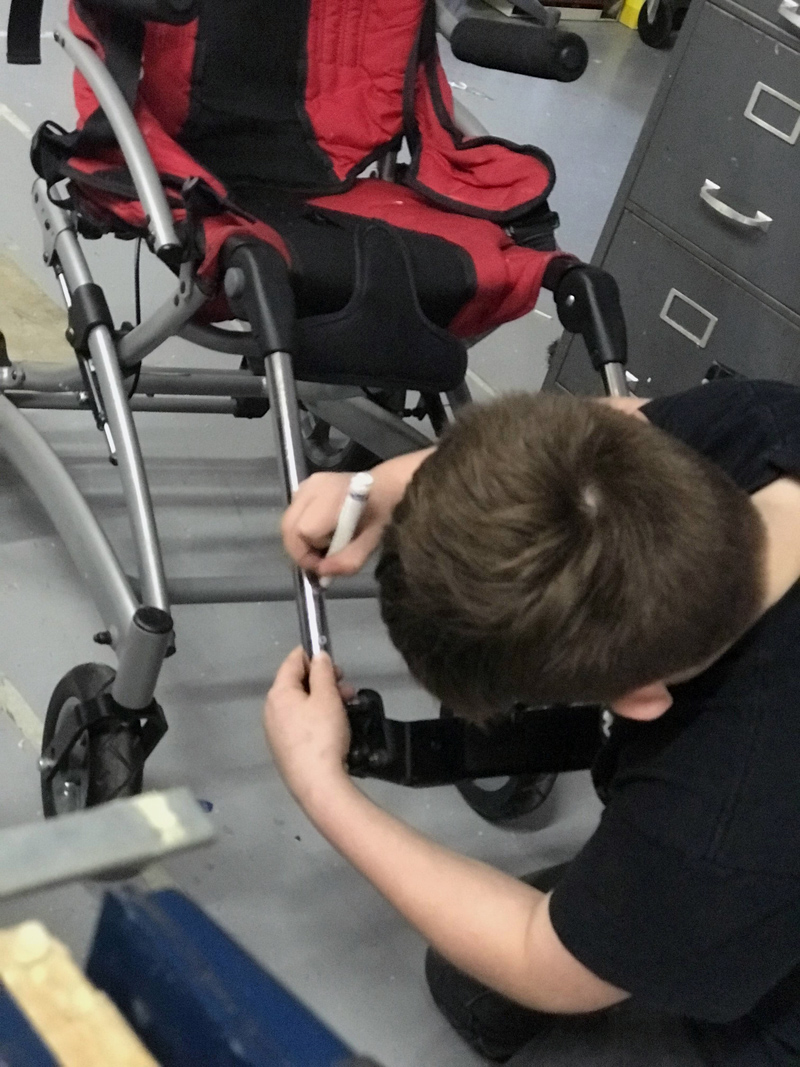 Camden Larrabee works on a pedal extension for a 12-year-old girl's wheelchair. (Photo courtesy Rachel Hamlin)