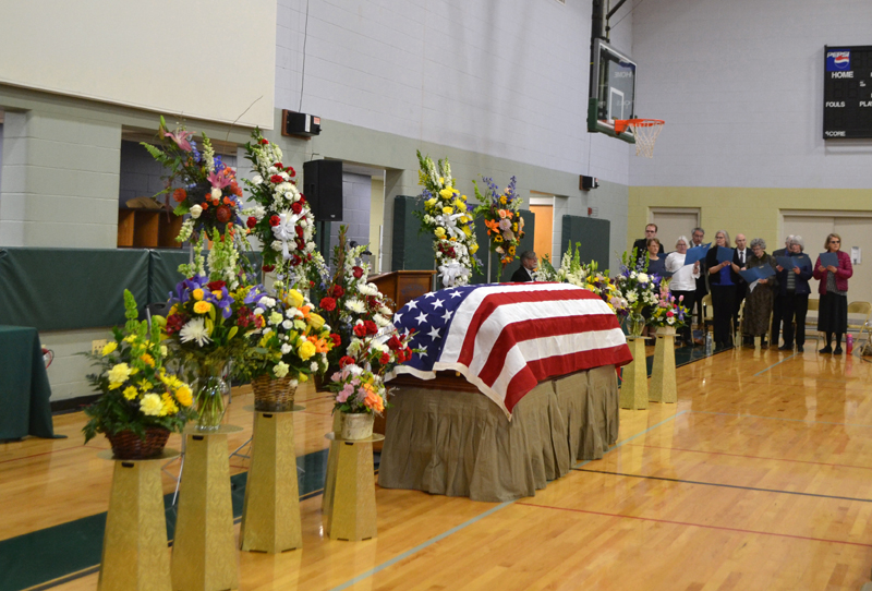 Flowers surround Roy Farmer's flag-draped casket during a memorial service at the Wiscasset Community Center on Sunday, April 7. Farmer, a local businessman and public servant for many years, died March 26 at the age of 91. (Charlotte Boynton photo)