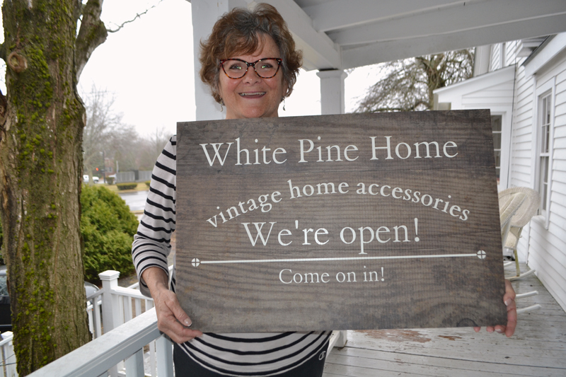 Betsy Kyle holds the sign she will soon mount on her home at 57 Washington St. to welcome customers to her new business, White Pine Home. (Charlotte Boynton photo)