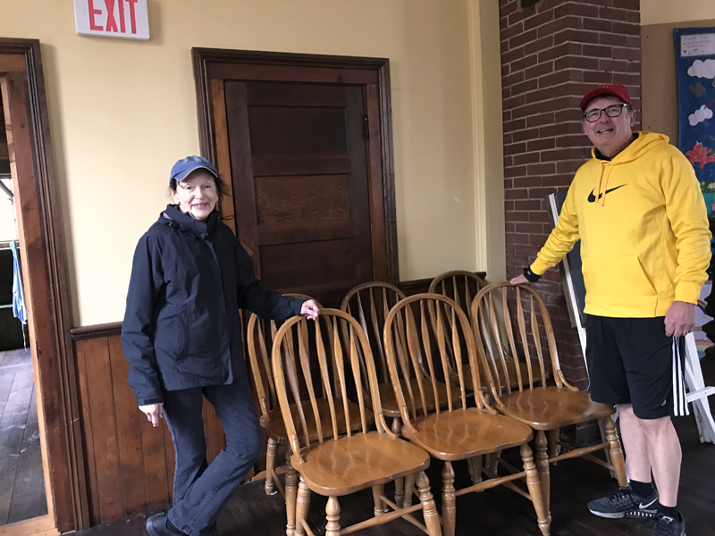 Round Pond Schoolhouse Association President Cynthia Wright accepts an early donation of solid-oak dining room chairs from the Stano family, of Round Pond.