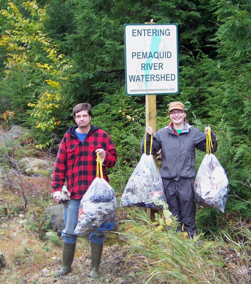 Cleanup volunteers tote bags of roadside trash.