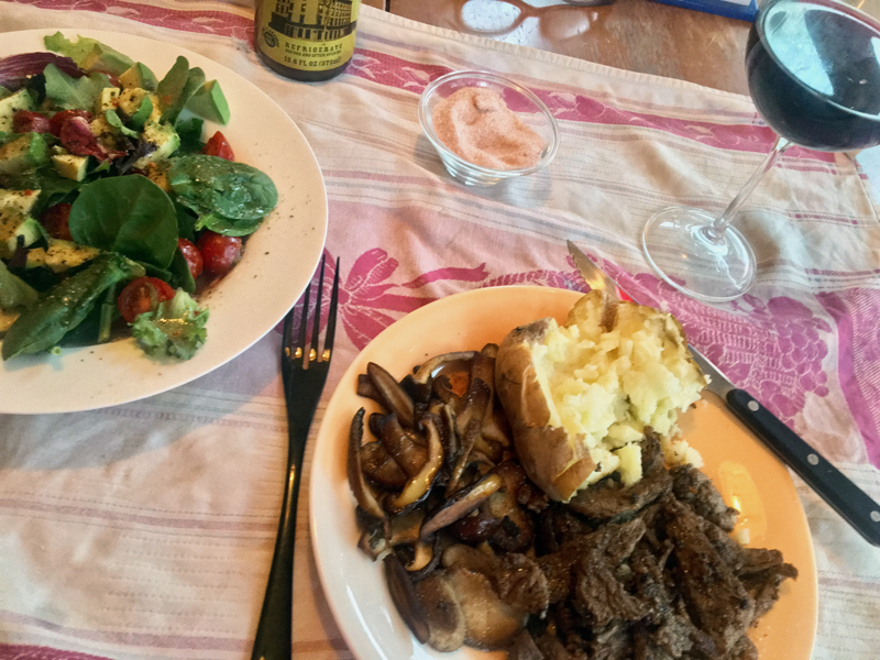 Sliced pan-fried New York sirloin with 'shrooms sauteed in butter, a baked potato, and a salad. (Suzi Thayer photo)