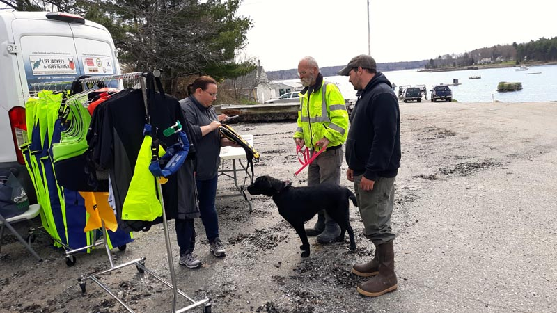 From left: Erin Lally, a representative of Lifejackets for Lobstermen, shows a personal flotation device to lobstermen Gary Clifford (with Maggie) and Brad Burns at Round Pond Landing on May 7. (Candy Congdon photo)