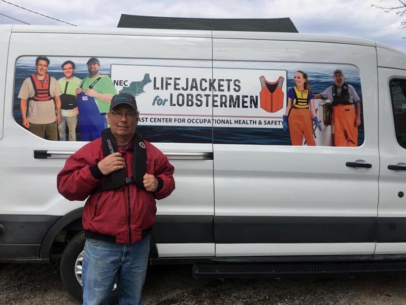Lobsterman and Round Pond Harbor Master Robert Ball models his new personal flotation device from Lifejackets for Lobstermen during the campaign's visit to Round Pond on May 7. (Photo courtesy Amanda Roome)
