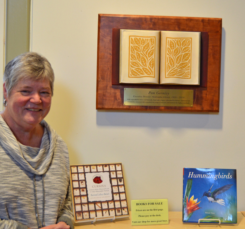 Skidompha Library Executive Director Pam Gormley stands next to her retirement gift, a plaque and sculpture by Damariscotta artist Jaques Vesery. (Evan Houk photo)