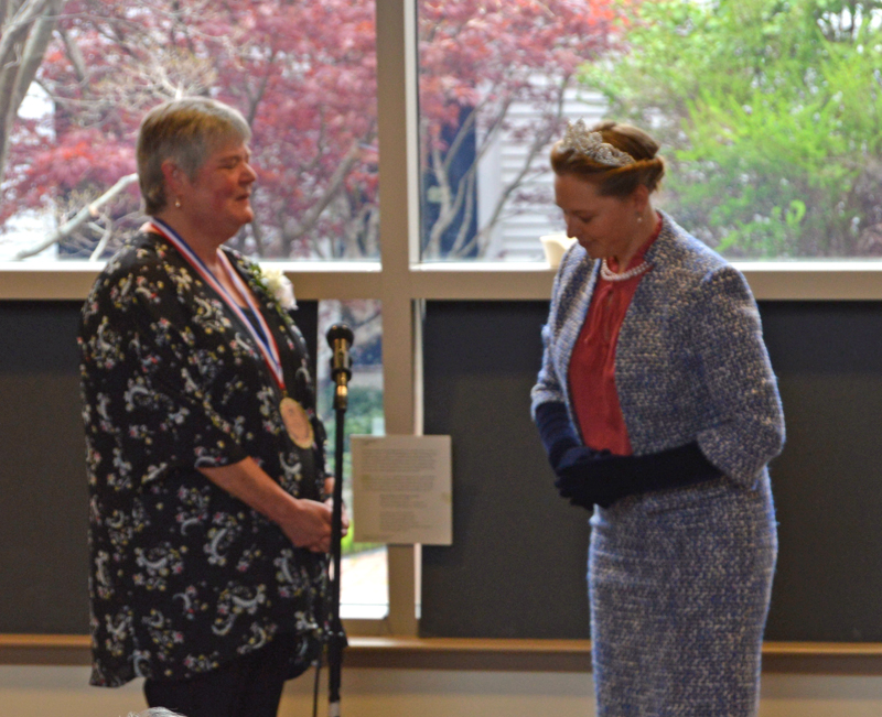 """""""The queen,"""" portrayed by former Skidompha Library employee Torie Delisle, bows after """"knighting"""" the library's retiring executive director, Pam Gormley, at a high tea in Gormley's honor Sunday, May 19. (Evan Houk photo)"""