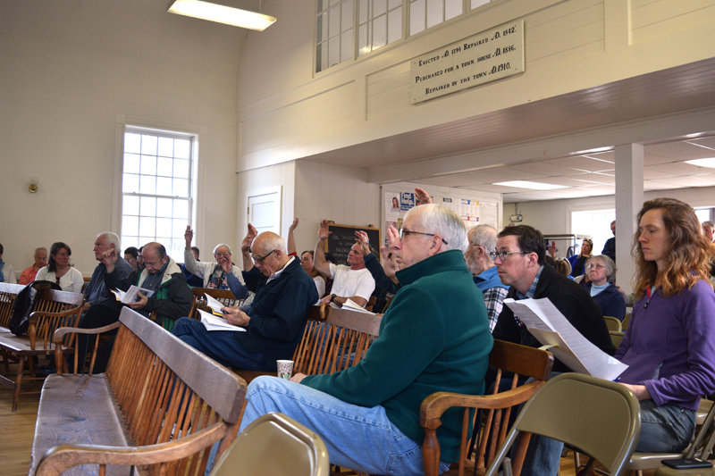 Edgecomb residents vote on an article in the early hours of town meeting. (Jessica Clifford photo)