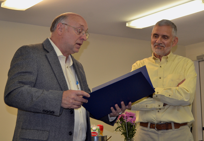 State Sen. Dana Dow (left) reads a legislative sentiment to Lincoln County Planner Bob Faunce during Faunce's retirement party at the Lincoln County Regional Planning Commission in Wiscasset on May 15. (Charlotte Boynton photo)