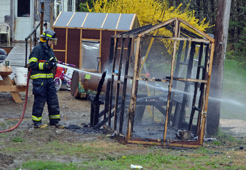 A Newcastle firefighter douses the smoldering remnants of a small chicken coop  at 20 Hawthorne Road in Newcastle the morning of Monday, May 20. (Evan Houk photo)