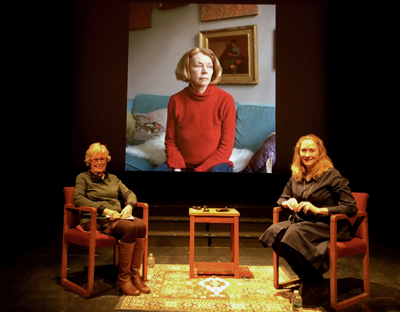 """Newcastle artist Jane Dahmen (left) chats with guest artist and photographer Jocelyn Lee on Thursday, May 2 during Dahmen's live interview event at Lincoln Theater in Damariscotta, Talking Art in Maine: Intimate Conversations. Behind Dahmen and Lee is a projection of a piece titled """"Bebe,"""" part of Lee's Personal Histories series. (Photo courtesy Lenin Sabino)"""