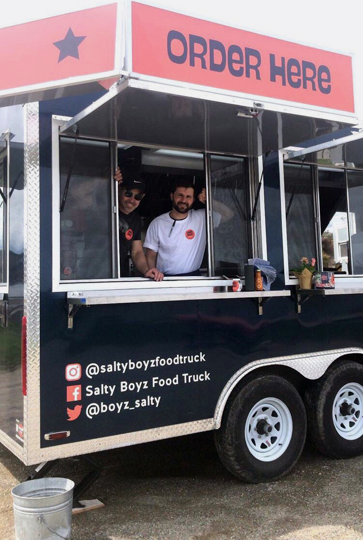 Warren Busteed (left) and Florin Ungureanu, owners of the Salty Boyz Food Truck, stand inside their new creation at Colonial Pemaquid State Historic Site. The food truck has set up shop at Popham Beach State Park through Labor Day. (Photo courtesy Warren Busteed)