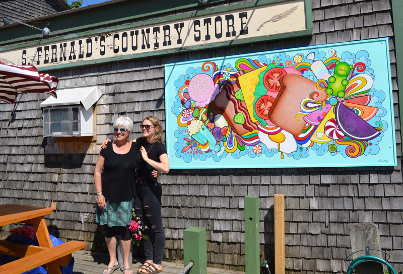 Edgecomb artist and educator Brady Nickerson (left) poses with Bremen artist Katie Riley after the unveiling of Riley's mural on S. Fernald's Country Store in downtown Damariscotta on Saturday, June 15. (Evan Houk photo)