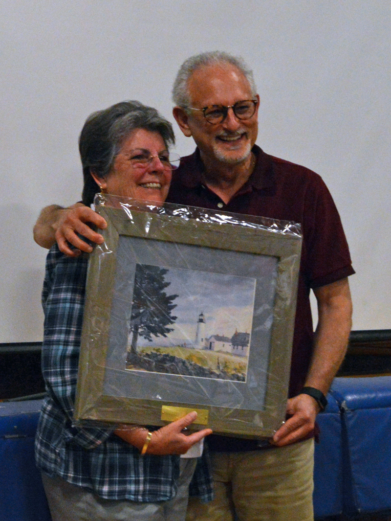 Damariscotta Board of Selectmen Chair Robin Mayer presents outgoing Selectman Ronn Orenstein with a portrait in recognition of his nine years of service at annual town meeting June 12. (Evan Houk photo)