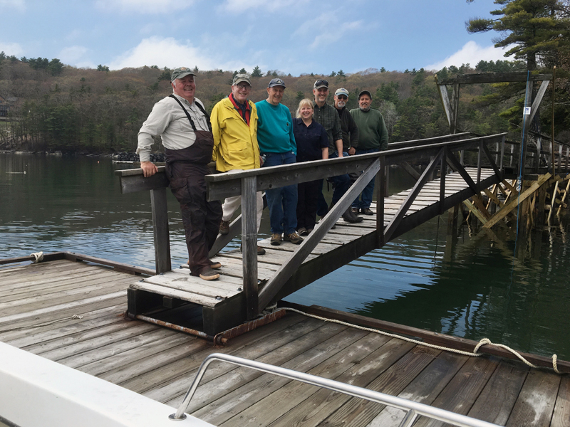 Volunteers and staff from Coastal Rivers Conservation Trust and the Maine Bureau of Parks and Lands made short work of installing the dock at Dodge Point on May 21. The reconstructed pier can be seen in the background. From left: Steve Spencer, Matt Filler, Chet Killam, Kim Lynch, Jesse Ferreira, Jim Grenier, and Glenn Kessler. (Photo courtesy Joy Vaughan)