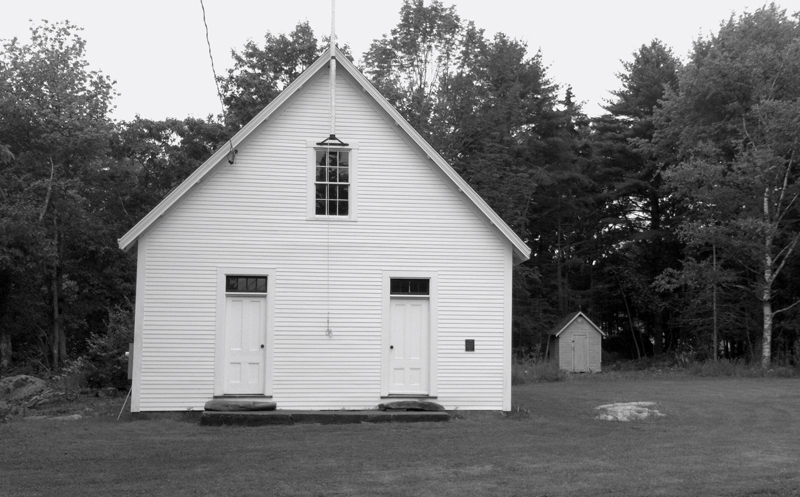 The S Road Schoolhouse and the old smokehouse on the edge of the woods to the right of the building.