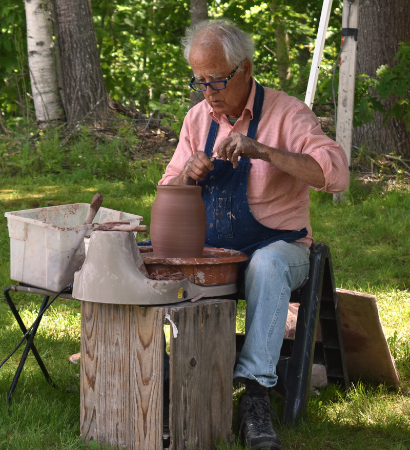 McCabe Coolidge, a potter based in South Thomaston, works at the Waldoboro Farmers Market on Saturday, June 22. (Alexander Violo photo)
