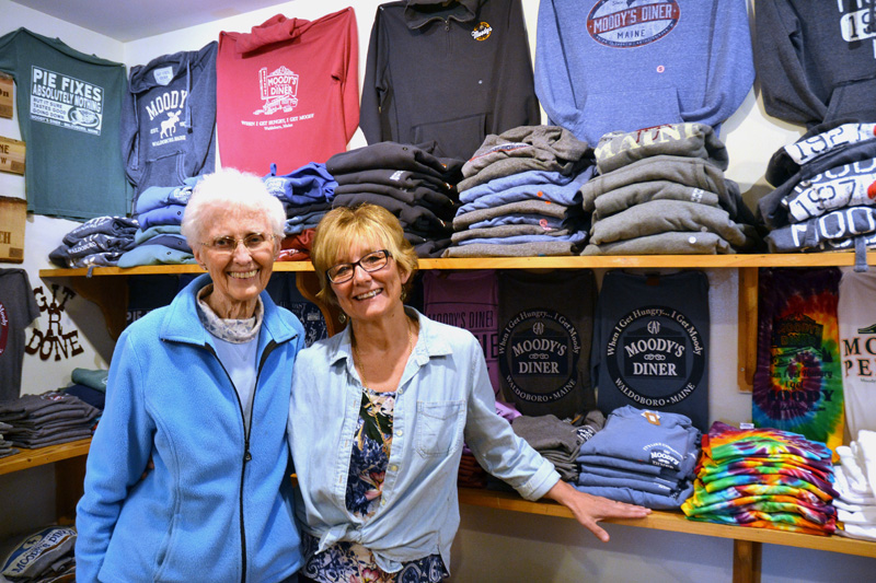Moody's Gifts owners Nancy Genthner and Mary Olson stand in front of a display of Moody's Diner T-shirts at their Waldoboro shop. The mother-and-daughter duo started the shop with their husbands more than 20 years ago. (Maia Zewert photo)