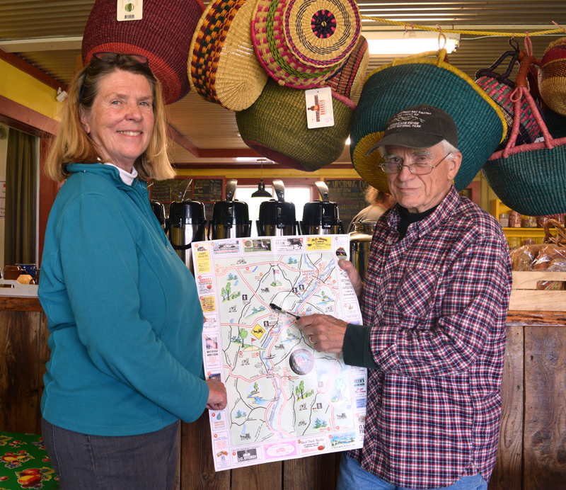 Libbey Seigars, one of the volunteers behind the new Whitefield map and guide, and Bill McKeen, Whitefield selectman and leader of the group, hold up an unfolded copy of the map. (Jessica Clifford photo)