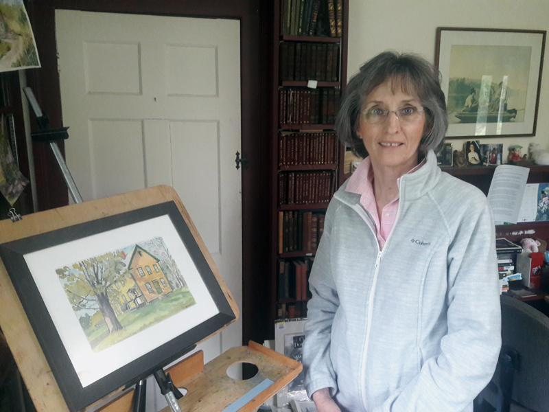 Lucy Martin, in her Whitefield home studio/library with one of her watercolor paintings, which will be exhibited in July at Sheepscot General Store.