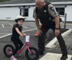 Lincoln County Sheriff's Office Sgt. Mark Bridgham teaches Lucy Leeman how to safely exit a driveway during a bicycle safety rodeo at Bristol Consolidated School on Saturday, June 22.