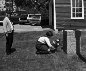 A Girl Scout at an early Memorial Day parade placing flowers at the Newcastle memorial at the corner of the old fire house, which is now the museum. (Photo courtesy Newcastle Historical Society museum)