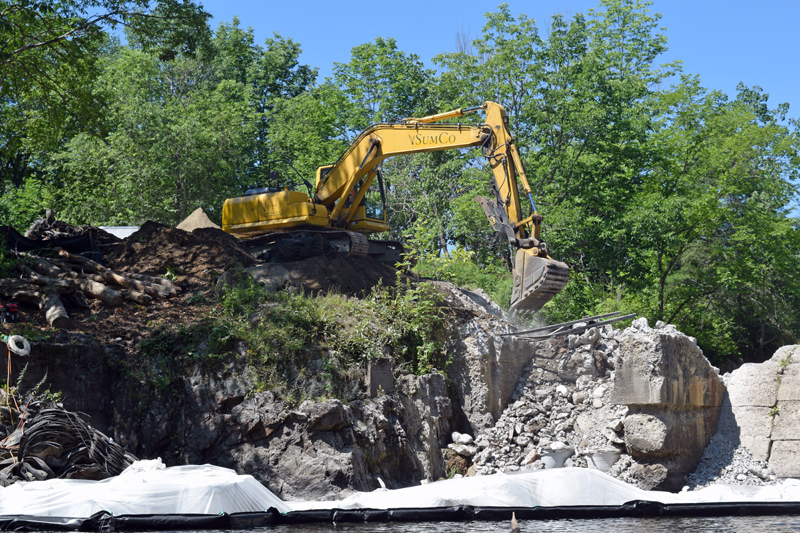 A backhoe begins to demolish the right abutment of the Head Tide Dam in Alna on Thursday, July 25. (Jessica Clifford photo)