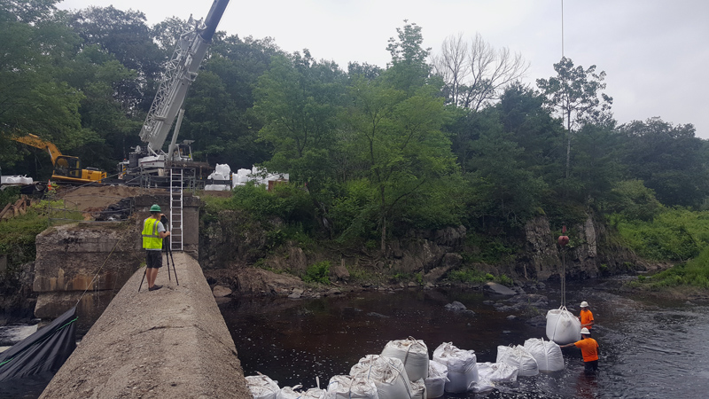 A crane lowers a sandbag into the river to isolate the work area before demolition of the abutment. (Photo courtesy Maranda Nemeth)