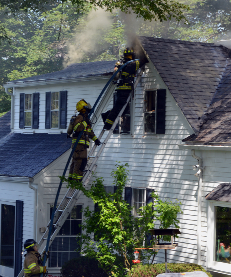 A firefighter attempts to douse the blaze at 26 Logan Road in Boothbay Harbor from the front side of the house after cutting a triangular hole in the attic wall with a chainsaw. (Evan Houk photo)