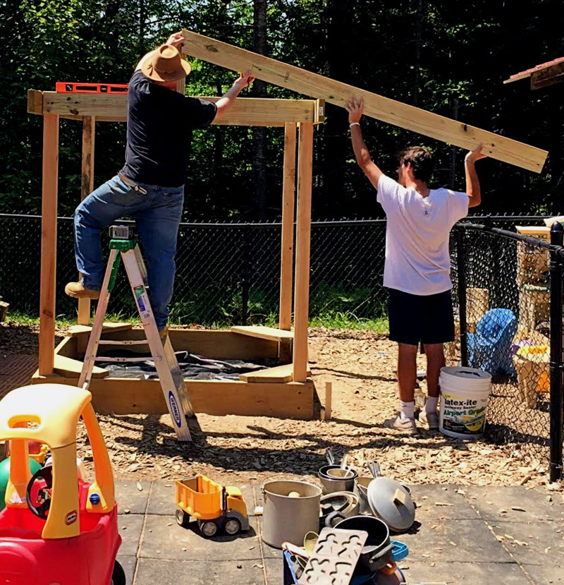 Shawn Chando (left) and John Giuliano build a shelter over a sandbox at Coastal Kids Preschool in Damariscotta on Tuesday, July 16. (Photo courtesy Lisa Conway)