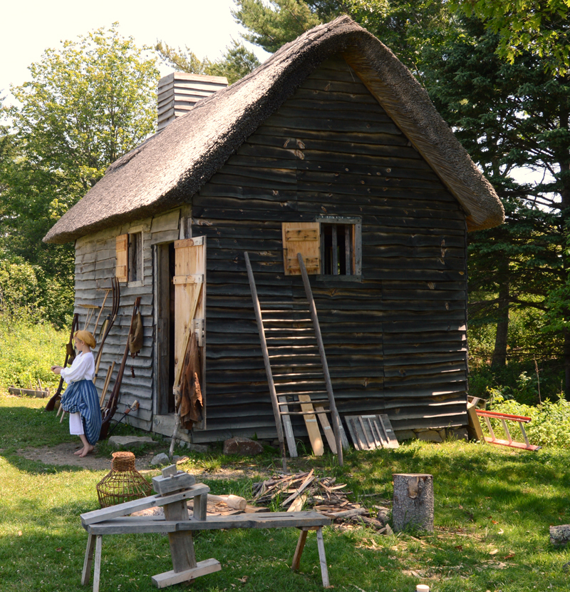 Addie Miller, granddaughter of Jeff Miller, the master blacksmith who is facilitating the living history exhibit, stands in front of the replica of a 17th-century fisherman's house at Colonial Pemaquid State Historic Site on Saturday, June 6. (Evan Houk photo)